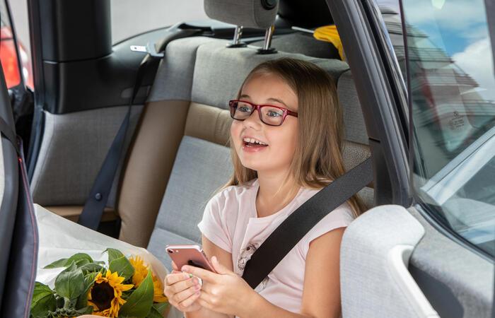 Flicka med telefon i bil